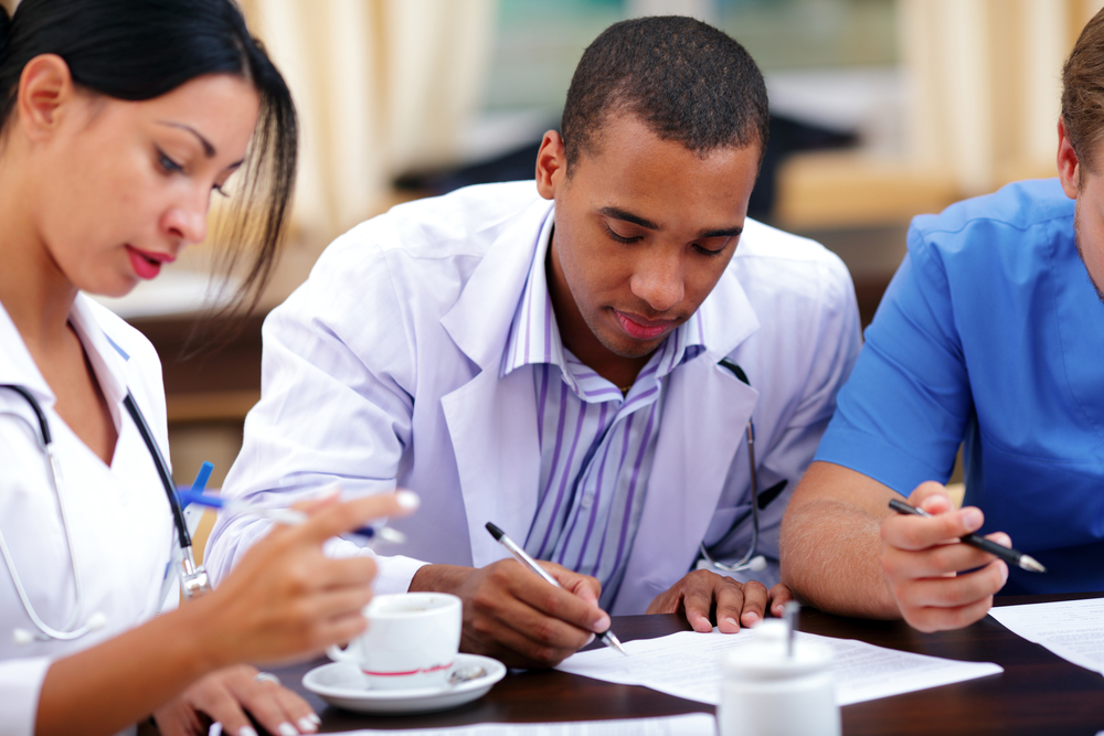Young african-american doctor making notes at the medical meeting