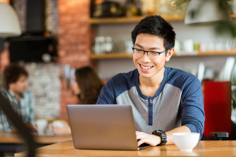 Young Asian male in a coffee shop, smiling at his laptop on the table.