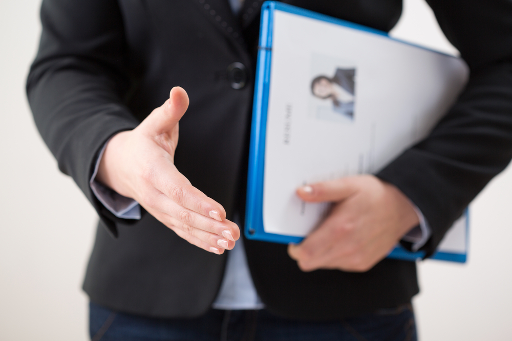 Man in a suit, carrying a resume under his upper arm and extending his other hand to shake another hand.
