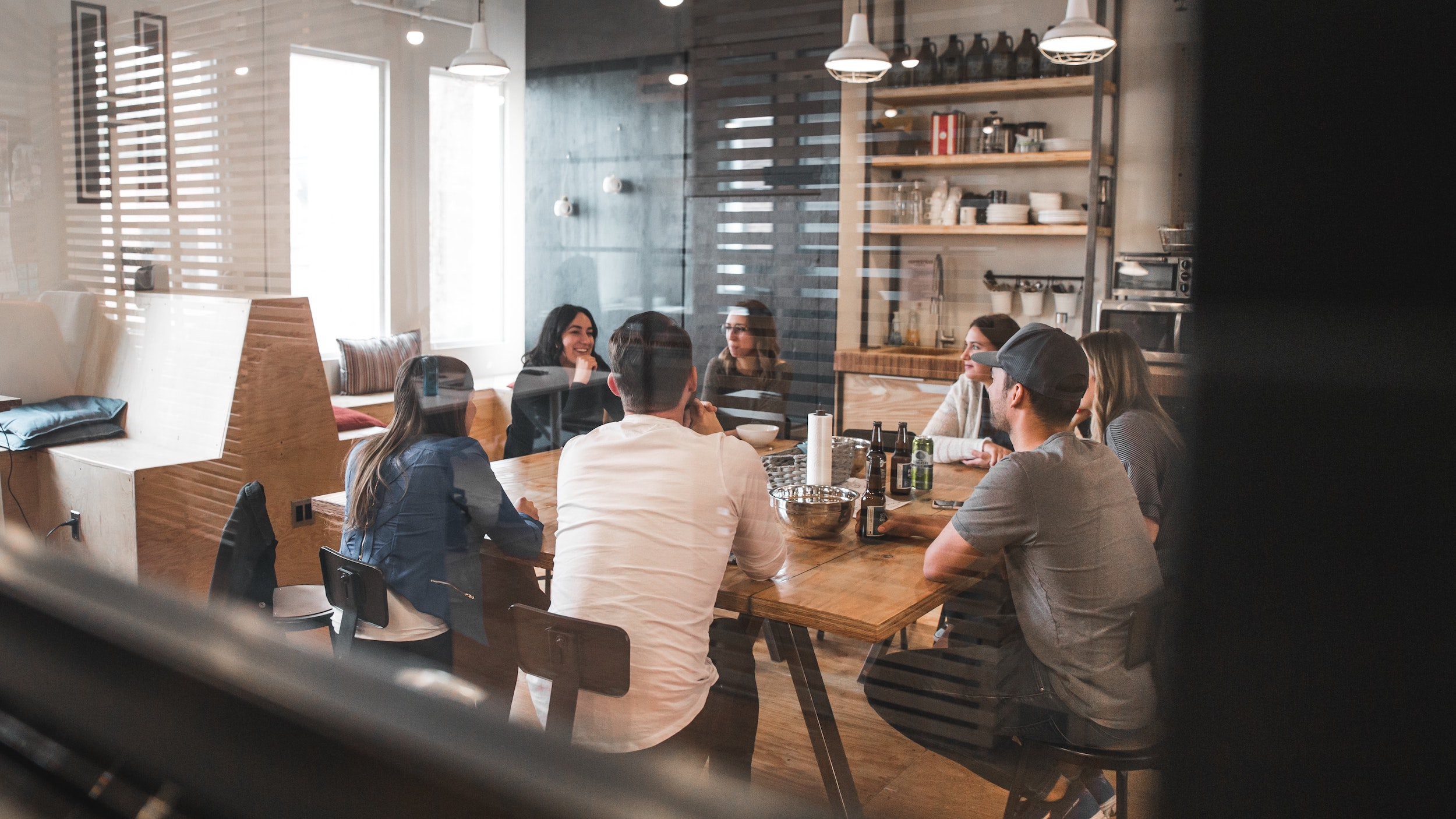 Group of employees working in a room together at a table.