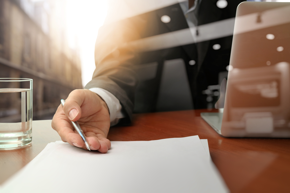 Man holding out a contract on a table